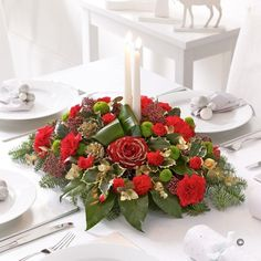This sumptuous arrangement of flowers and foliage is a fitting decoration for the Christmas dinner table and is sure to be admired by all. We've chosen festive red flowers and a selection of seasonal foliage and added a pair of slim, tapered candles and a dusting of glitter.