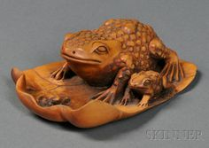 Wood Carving, Japan, 19th century, depicting two toads and a beetle on a delicately furled lily pad, lg. 3 5/8 in.