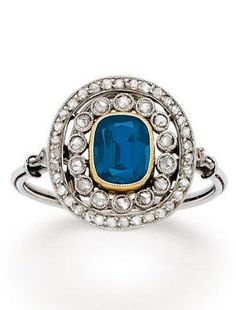 A Belle Époque Sapphire and Diamond Ring, circa 1910. Centring a cushion-shaped sapphire amid a delicate double surround of rose-cut diamonds, mounted in platinum, with French assay marks.