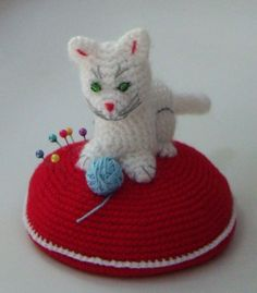 """Crocheted pin cushion """"Snow white kitten with ball on red cushion"""". $21.00, via Etsy."""