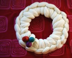 """Thought of this last night as I was falling asleep.  SO quick and easy!!  Materials: -one 12"""" wire wreath ring (styrofoam round ones should work, but might get hung up on the wool a lot) -approx 12-16oz wool top (I had plain white right at hand, hand dyed might be pretty) -Wool felt balls, or any other decorative thingies you want on it  Instructions: single crochet your wool top around the wreath ring, using your fingers as your hook.  This site has good illustration of how. It is really…"""