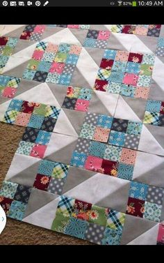 scrappy quilt flowing together with grey& white Stripes