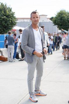 Acheter la tenue sur Lookastic:  https://lookastic.fr/mode-homme/tenues/blazer-gris-t-shirt-a-col-en-v-blanc-pantalon-chino-gris-chaussures-de-sport-gris/13136  — T-shirt à col en v blanc  — Blazer en laine gris  — Pantalon chino gris  — Chaussures de sport grises