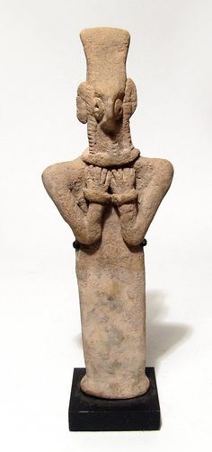 Syro Hittite terracotta Astarte idol, 2000-1500 B.C. With columnar body and hands pressing against her chest, she wears a tall headdress, the facial features are bird-like with large circular eyes and angular nose, coils of hair framing the face in front of what appear to be ears and she wears necklace with pendant and bracelets, 20 cm high. Private collection