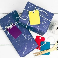 Educational star constellations wrapping paper set for childrens birthday party gifts or unique christmas giftwrap. Gorgeous night sky kraft paper with bright colourful tags.  Kraft-look dark blue wrapping paper showing the different star constellations with their names. This lovely