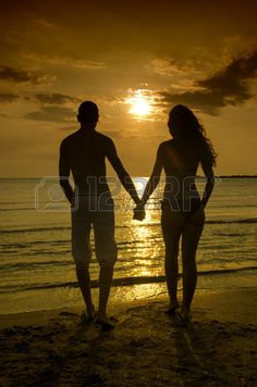 Couple enjoying their time at the sunrise on the beach couple holding hands in a romantic scene silh Stock Photo