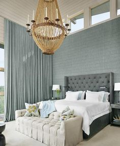 Blue and grey bedroom features a shiplap vaulted ceiling over blue fabric clad walls lined with a gray velvet tufted bed dressed in white bedding and sky blue shams flanked by gray nightstands illuminated by iron floor lamps.
