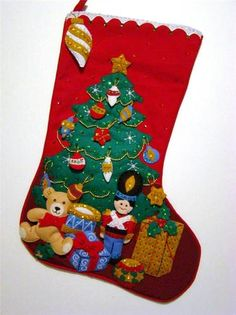 "This hand~crafted 21"" Christmas Stocking called ""Under the Tree"" is made of felt applique on cloth (not felt) and beautifully decorated with hand sewn sequins and beads. Portions of this stocking are stuffed creating a three dimensional apperance. It measures approx. 21"" diagonally and 10"" across the top, so there is lots of room to stuff."