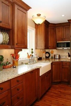Outdated cabinetry was replaced with new two-toned, full-overlly, and full-height cabinets. A wood flyover above the central island ties it to the rest of the cabinetry. A beadboard panel and corbels on the back of the island, an apron sink, and an exposed plate rack add traditional details to the space.