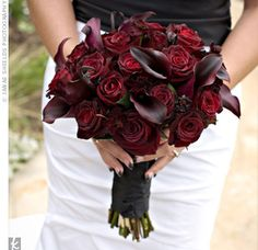Dark red roses and black calla lilies.  Love how they stand out against the black sash and her white dress.