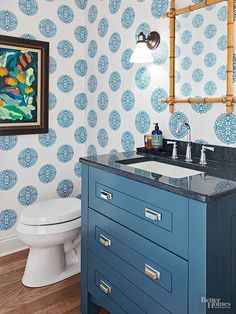 Temper multiple shades of blue with monochromatic accents. In this powder room, blue patterned wallpaper provides a fun backdrop for a painted vanity in a similar shade. The bathroom's artwork incorporates both blue and black for a cohesive color scheme./