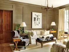 The study's lime-washed paneling, made of oak reclaimed from the property, is complemented by a gilt-wood chandelier by Vaughan; a Suzanne Kasler for Hickory Chair sofa is joined by a Scalamandré wing chair upholstered in a Rogers & Goffigon velvet, and the antique armchair is clad in an Old World Weavers tiger stripe | Greys, white, black, woods. Lovely neutrals.