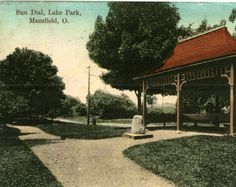 White gravel walkways lead to a rough cut sun dial in Lake Park. Behind the sundial is a small pagoda type shelter containing benches. The B & O Railroad is visible in the rear.