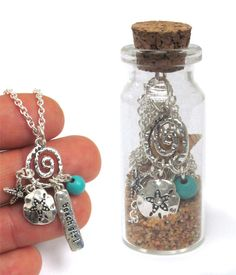 "16"" Necklace with beach inspired charms in a glass bottle with sand."