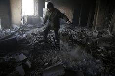 A man stands in the rubble of the aftermath of Russia-Ukraine conflict.