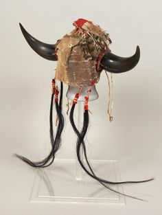 "Headdress consists of a hide skull cap with a seed bead band in front with white ground and two red triangles at either side and a dark blue triangle in the center. There are remnants of hide streamers and a brass bell at each temple. A black buffalo horn protrudes from each side. The top has tattered feathers wrapped in red trade cloth. At the bottom, back hangs long black horsehair ""streamers"" wrapped in red trade cloth."