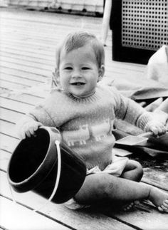 An adorable Prince Harry playing on the deck of the royal yacht Britannia, just shy of his first birthday