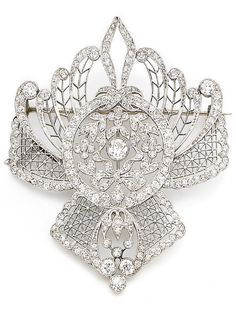 *A belle époque - edwardian diamond brooch, circa 1910 The central garland motif collet-set with an old brilliant-cut diamond to a finely pierced openwork latticework surround, set throughout with similarly, rose-cut and cushion-shaped diamonds, old brilliant and cushion-shaped diamonds approx. 3.10cts total, French assay mark, later brooch fitting, length 5.8cm