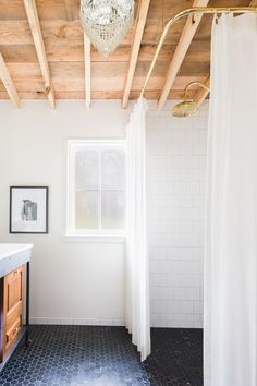 """The color black is used throughout the house, including in the bath. """"The dark hexagon tile packs a lot of punch in a small space,"""" notes Arnold. After the rough-hewn cedar ceiling was installed, he and Denton decided it was perfect in its natural state. """"It had the feel of an exterior porch that went along with our deconstructed look,"""" says Arnold. The textured wood makes a great backdrop for the antique crystal chandelier."""