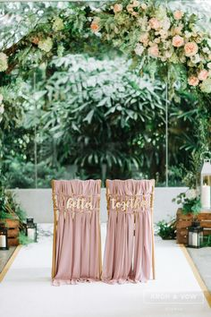 Gorgeous blush pink chairs for the bride and groom under a green and pink wedding arch