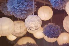 Petit astuce pour rendre votre deco mariage encore plus chaleureuse et féerique : pensez à suspendre de la décoration au plafond comme ici avec des boules lumineuses et des pompons violets.