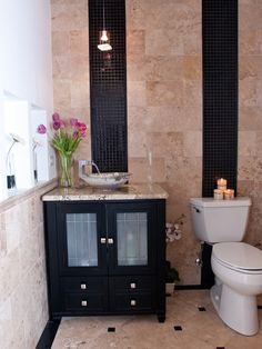 Stone bath with black mosaic glass tile floor border, accents, and stripes up the walls! Striking, unique, and elegant use of glass mosaics!