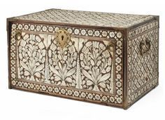 A LARGE IVORY-INLAID CABINET GUJARAT OR SINDH, WESTERN INDIA, LATE 17TH OR 18TH CENTURY. Of rectangular form, heavily inlaid with ivory panels, the fall front with three large floral sprays within arches between cypress trees, the top, side and back with a lattice of four-petalled rosettes and cross-shaped motifs, the front with two ring handles opening to reveal seven drawers, the corners with brass mounts, the sides with handles, with lock and key, restored
