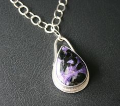 Charoite Pear shaped Pendant necklace in Sterling Silver Setting/Purple/Black Swirl Pattern    A stunning, large and very well polished Charoite gemstone is the focal point of this sterling silver pendant necklace. This Charoite gemstone is comprised of beautiful swirls of deep purple, lilac and black coloring. Ive encased this beauty in a fine silver bezel setting and extended the silver back plate to add a ledge around the stone with a hammered ribbed effect for added interest. A 5 mm…