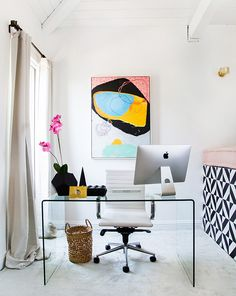 An abstract art piece radiates above the clear desk in the office corner of Shay Mitchell's home.