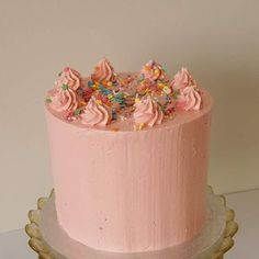 Four layer vanilla cake with layers of raspberry and pink swiss meringue buttercream, decorated with sprinkles!