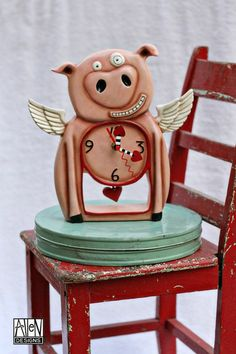 """When pigs fly!? Well this little winged guy sure can! """"The Little Piggy"""" Hand painted Resin Clock can wall hang or stand alone. Swinging heart pendulums add lots of charm. This smiling guy has so much personality! What a funky valentines or anniversary gift he would make! $59 at Quirks of Art."""