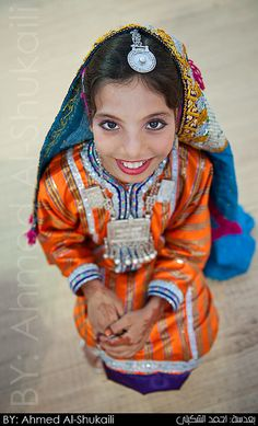 a young Omani girl wearing the traditional Omani dress from (Dakhlia), most of the traditional omani dresses are colorful with bright colors.