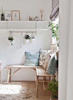 entryway with light wooden bench, plants, and white shelf