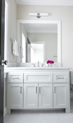 lovely guest bathroom features double-light sconce illuminating white parsons mirror over white washstand topped with white marble atop vintage hex tiled floor.
