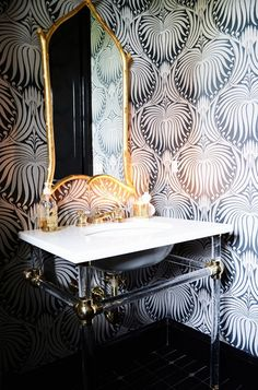 Powder room with gold mirror and Farrow & Ball Lotus wallpaper.