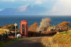 Road with remote telephone box and sheep beside it looking over the sea to the isles of Eigg and Rum