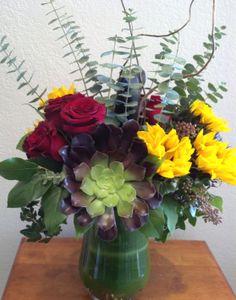 A cheery flower arrangement for any occasion. #succulents #sunflowers #roses #eucalyptus #flowerarrangement #flowerbouquet