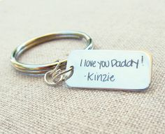 A rectangular (26mm x 10mm) shaped sterling silver key ring that has ACTUAL handwriting engraved on one or both sides. These make a wonderful gift for your h
