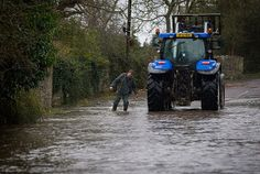A farmer checks the depth of flood water in Thorney, Somerset.
