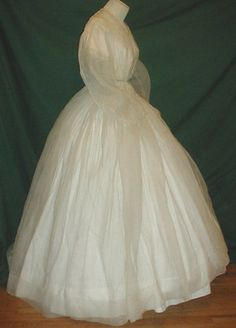"""Gossamer 1860's two piece gauze dress, de-accessioned from NY city museum. Fabric has scattered tiny aqua blue dot pattern.  Bodice line with cotton camisole [not a """"camisole""""; it's just an attached lining] that has short lace trimmed sleeves & front hook & eye closure.  Neck, shoulders, armscyes are piped.  Skirt unlined.  Bust: 30""""; Waist: 22""""; skirt length: 43""""; width at hem: 174""""."""