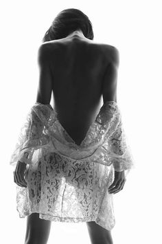 Well done black and white shot. Made from the back, semi-nude model, lace falling around her lower arms, torso down to her knees, thin lace showing the form of her body. Very sensual and erotic.