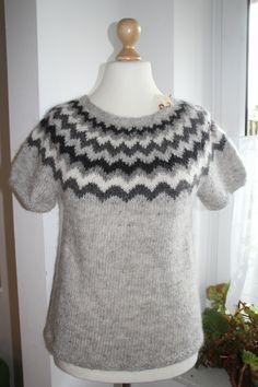 Dieser Pullover mit kurzen Armen wurde aus original Islandwolle mit einem wunderschönen Einstrickmuster handgestrickt.    100 % Wolle    handgestrickt    Größe: M  Länge: ca. 61 cm  Breite (unter den Armlöchern ...