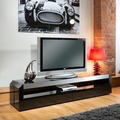 Modern TV cabinet/entertainment unit black gloss with glass top 701F. Features include beautiful design, 2 drawers and space for AV equipment. The quality is of this product is absolutely superb with aluminium trim and black glass top. Call 02476 642139 or email sales@quatropi.com or visit www.quatropi.com for additional information.