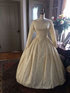 """Vintage late 1950s to early 1960s ivory brocade wedding dress. Scoop neckline, long fitted sleeves and full skirt with wide train. Shown over a hoop and without. (Hoop not included). Buttons up the back and on sleeve cuffs. There is a small tear near the hem and some soiling on the skirt hem, mainly on the underside of the train, otherwise in very good condition. Petite size with Approximate measurements of bust 38"""", waist 27"""", sleeve underarm length 16"""" skirt length in front ..."""