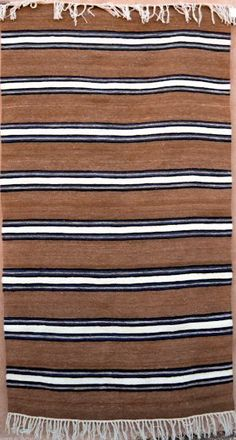 """Desierto"" by Beatrice Maestas Sandoval, handspun churro, brown sheep colors with indigo-dyed blue. Rugs On Carpet, Carpets, Navajo Rugs, Churro, Striped Rug, Indigo Dye, Kilims, Rio Grande, Fabric Art"