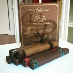 Rocky Patel Java Sampler features three cigars from the Java Collection by Rocky Patel and Drew Estate. The Nicaraguan long filler tobaccos are infused with the delicious flavors of Java coffee, vanilla and mint, finished with dark Brazilian wrappers.  you'll swear you're sipping on your favorite cup of coffee. #Rockypatel #drewestate #cigars #java #sotl #botl Rocky Patel Premium Cigars #myrpstory Montecristo Cigars, Cohiba Cigars, Ashton Cigars, Drew Estate, Premium Cigars, Java, Pipes, Beverage, Coffee Cups