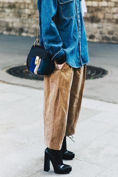 A denim shirt is paired with suede pants, platform boots, and a Chloé saddle bag