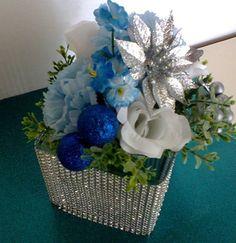 Arranjo de Flores Artificiais de Seda : Rosas Brancas , Cravos azuis ,folhagens , em Vaso de Vidro retangular decorados com strass e com bolinhas de Natal, e um lindo enfeite de Natal prata. R$ 40,00