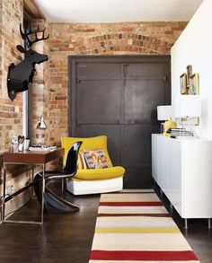 LOVE the deer head, striped carpet for a splash of color and the rustic door with the brick!