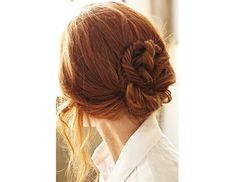 This twisted sailor's knot bun with loose strands in front looks both preppy and romantic.
